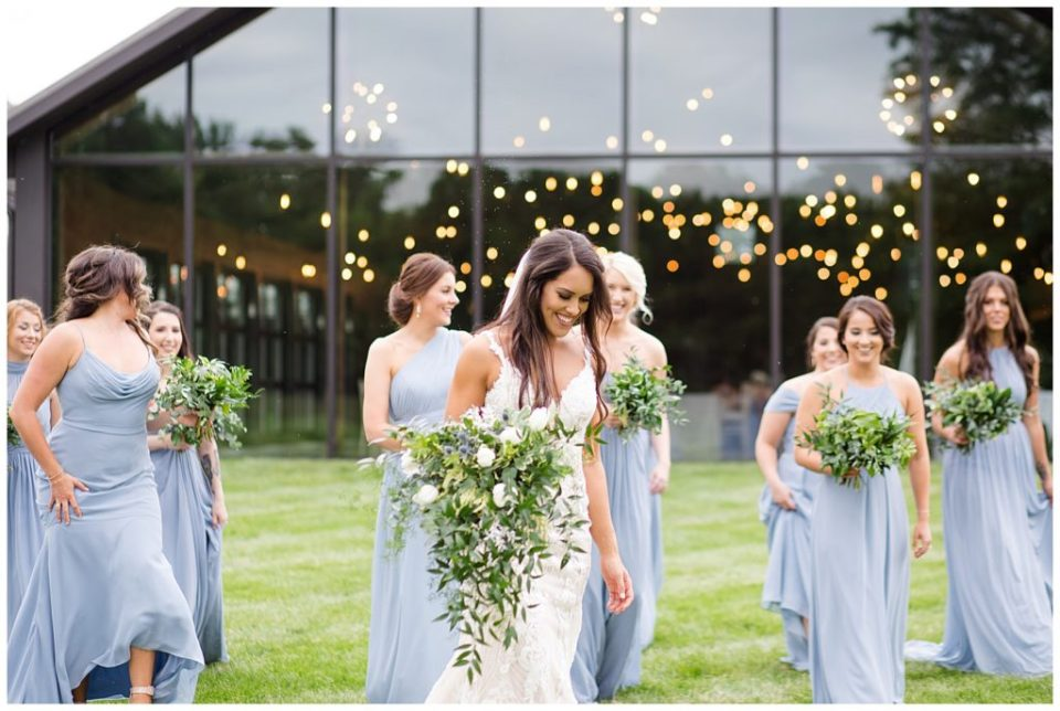 An image of the bride and bridesmaids relaxing together in front of the wedding reception venue at an Jorgensen farms Oak Grove wedding venue by Columbus Ohio wedding photographer, Alayna Parker Photography