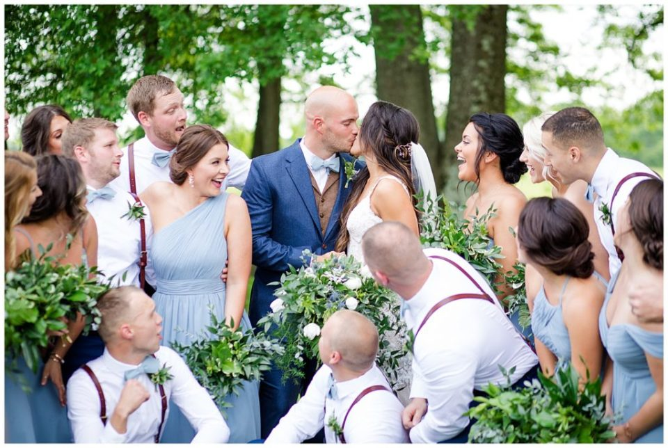 A picture of the bride and groom kissing as the wedding party relaxes and cheers them on after the wedding ceremony at an Jorgensen farms Oak Grove wedding venue by Columbus  wedding photographer, Alayna Parker Photography