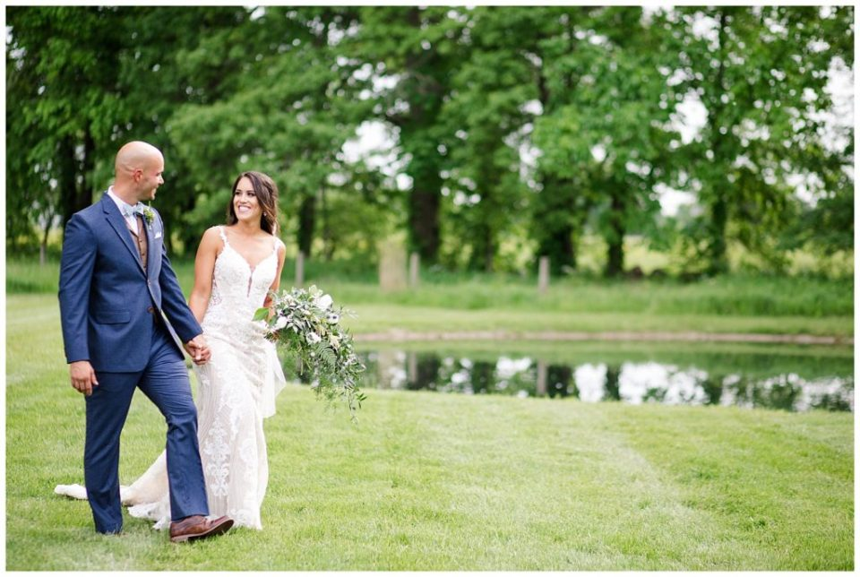A picture of the bride and groom smiling and walking in a beautiful outdoor setting at the Oak Grove wedding venue by Columbus  wedding photographer, Alayna Parker Photography