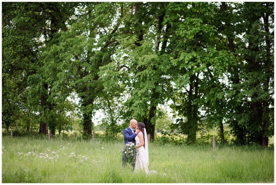 A photograph of a long-range view of a bride and groom kissing in a beautiful field lined with trees at the Oak Grove wedding venue by Columbus OH wedding photographer, Alayna Parker Photography