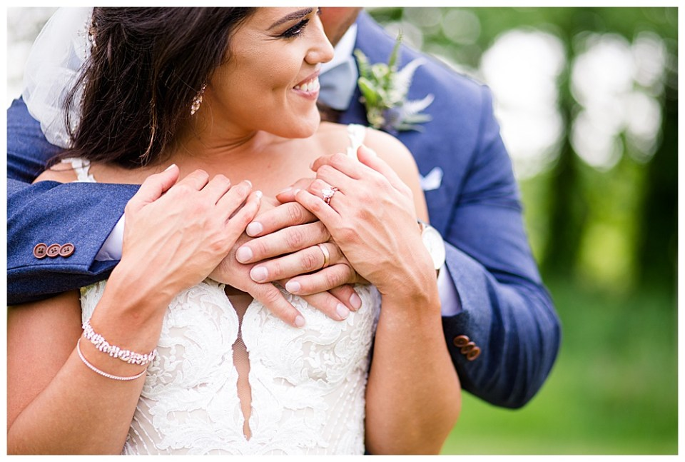 An image of a closeup view of the groom embracing the bride from behind as she smiles and grasps his hands at the Oak Grove wedding venue by Columbus Ohio wedding photographer, Alayna Parker Photography
