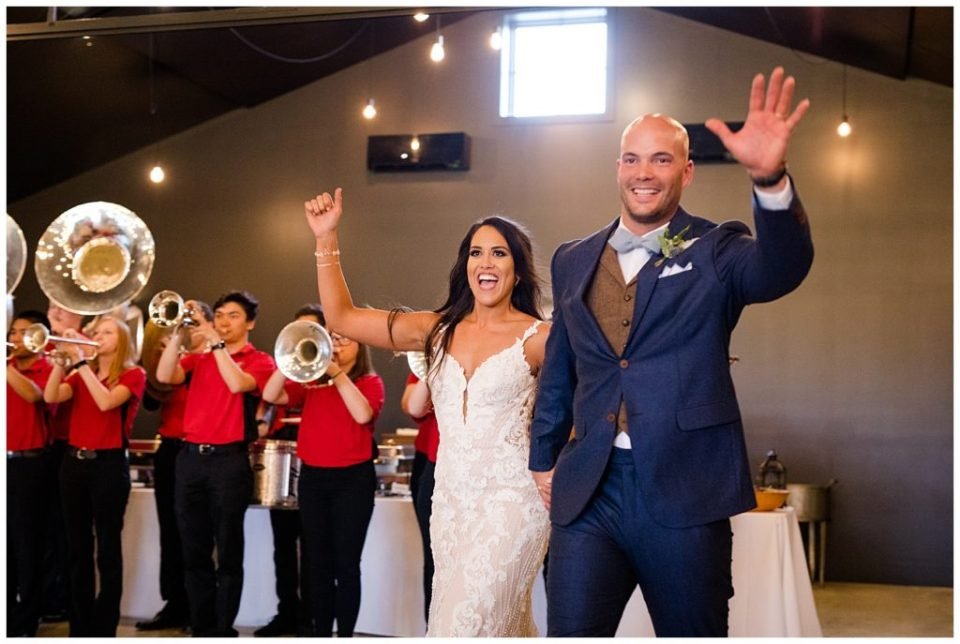 An image of the bride and groom waving and entering the wedding reception party as they're introduced with a band playing at the Oak Grove venue in New Albany, Ohio by Columbus Ohio wedding photographer, Alayna Parker Photography