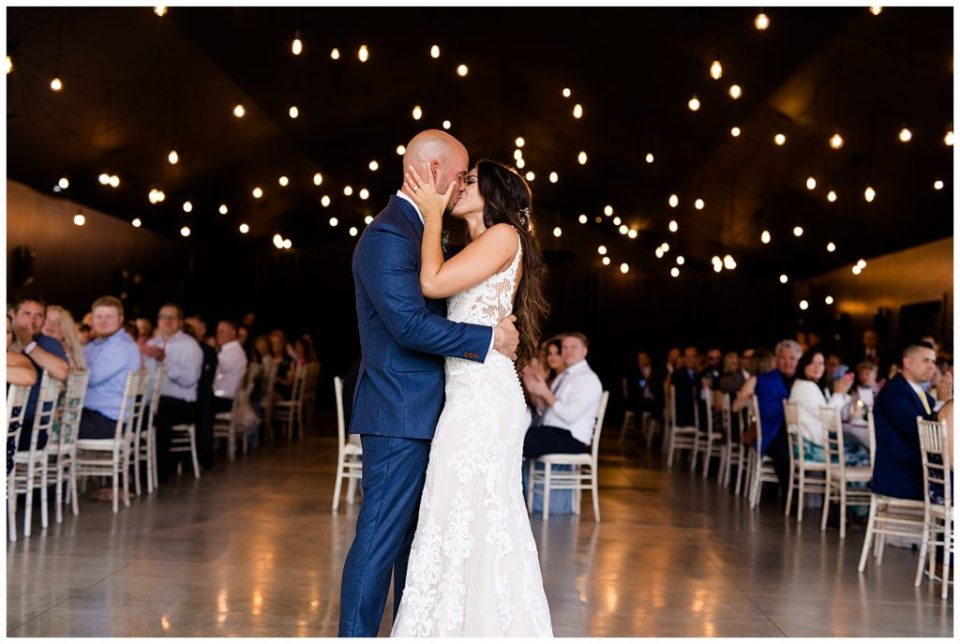 An image of the bride and groom kissing as they end their first dance at the wedding reception while the guests look on and clap at the Oak Grove wedding venue by Columbus Ohio wedding photographer, Alayna Parker Photography