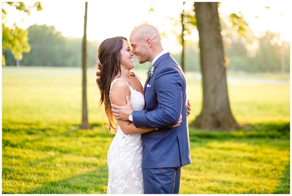 bride and groom smiling at each other during golden hour at jorgensen farms oak grove