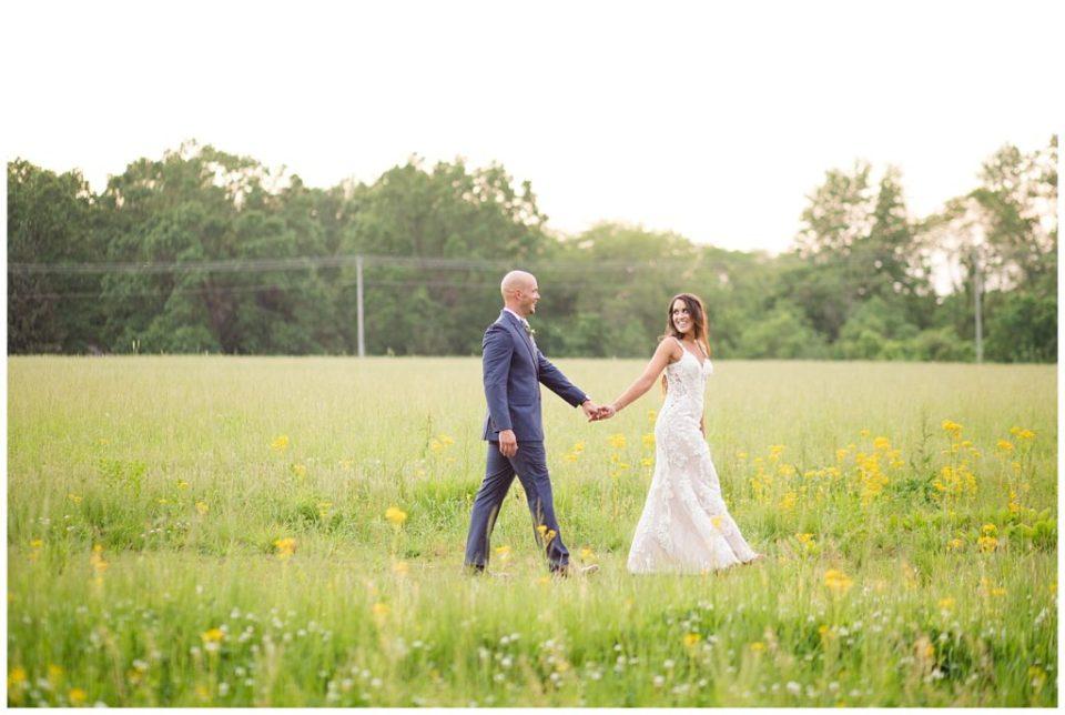 bride and groom walking through field during golden hour at jorgensen farms oak grove
