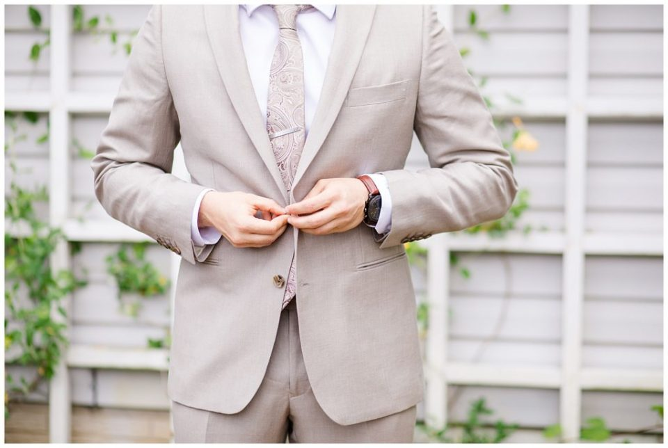 A photograph of a groom buttoning his tuxedo jacket as he is getting dressed for his wedding ceremony at Jorgensen Farms wedding venue by Alayna Parker  - Columbus OH wedding photographers