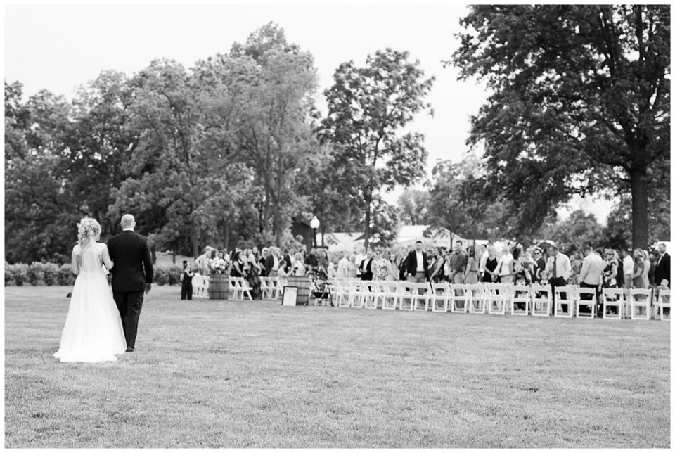 A picture in black and white of a bride and her father approaching the aisle in an outdoor wedding with the guests looking on at Jorgensen Farms wedding venue by Alayna Parker Photography  - Columbus  wedding photographers