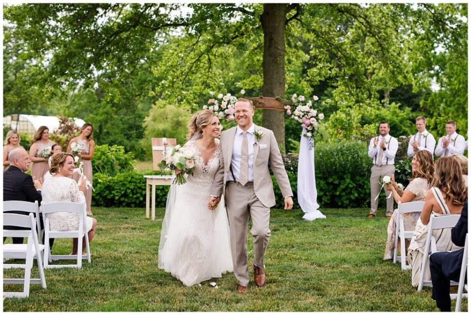 A picture of a bride and groom smiling joyfully as they walk down the aisle as their wedding ceremony ends and the guests clap at Jorgensen Farms wedding venue by Alayna Parker Photography  - Columbus  outdoor wedding photography