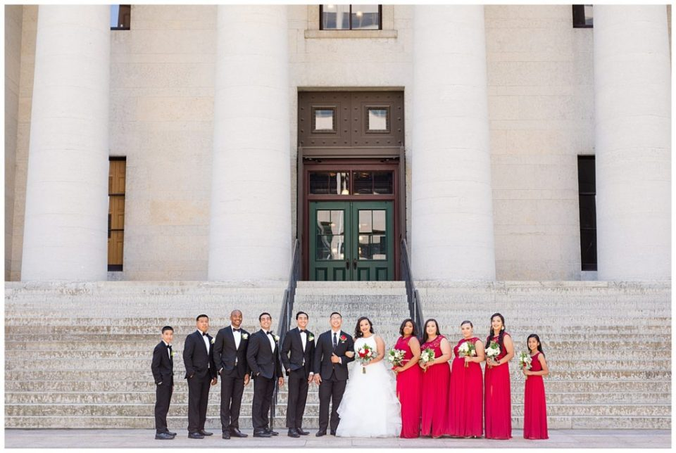 A photograph of a long-range view of the wedding party lined up and smiling in their wedding attire by Columbus OH wedding photography specialist, Alayna Parker Photography