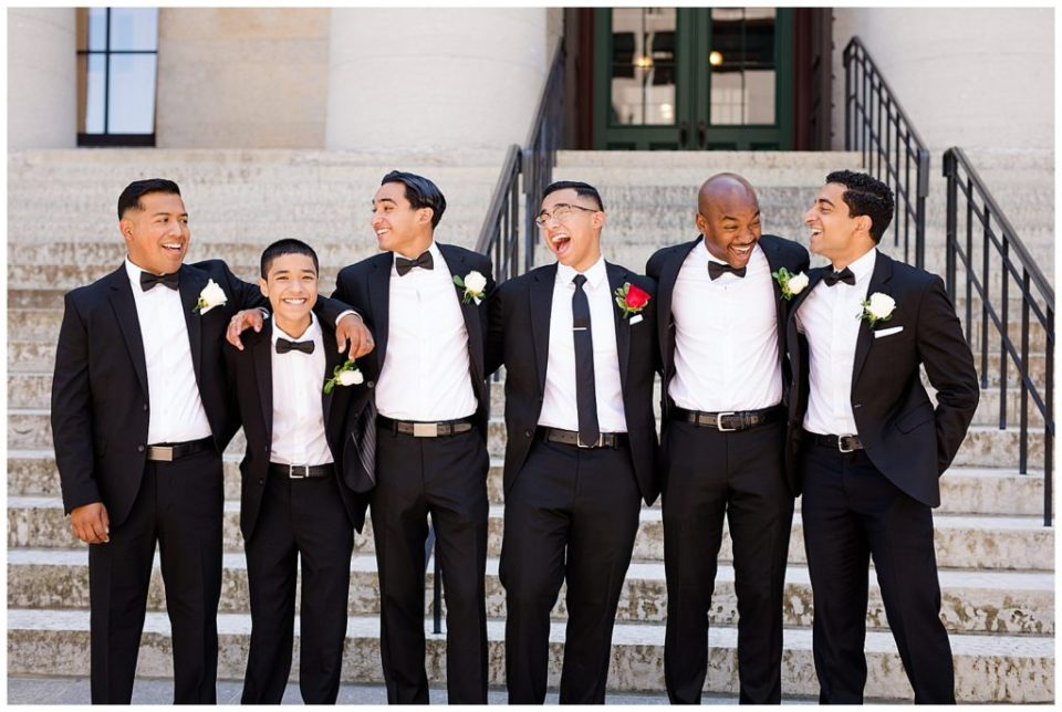 A picture of the groom lined up with his groomsmen in their tuxedos, relaxed and laughing together by Columbus  wedding photography specialist, Alayna Parker Photography