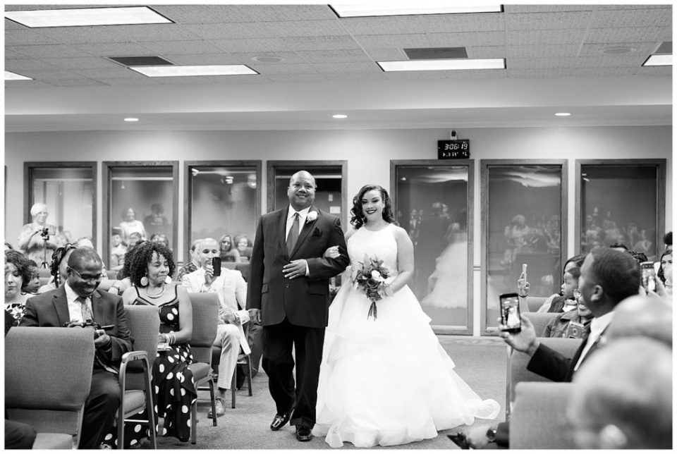 A photograph of a black and white view of the bride walking down the aisle with her father as the guests look on by Columbus OH wedding photography specialist, Alayna Parker Photography