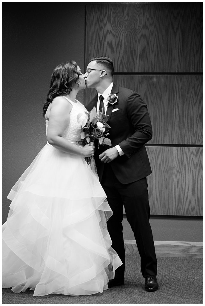 A picture of a black and white view of the bride and groom's first kiss after their vows at their wedding ceremony by Columbus  wedding photography specialist, Alayna Parker Photography
