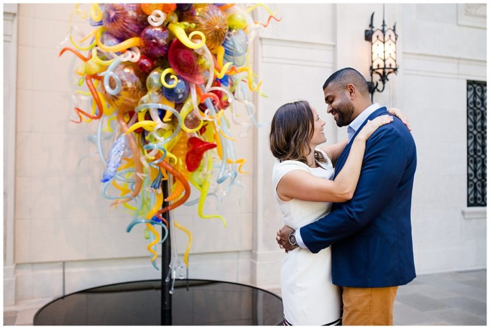 A photograph of an engaged couple holding each other and smiling happily as they stand next to a modern sculpture in an art museum setting at the Columbus Museum of Art by Alayna Parker  - Columbus OH engagement photographer