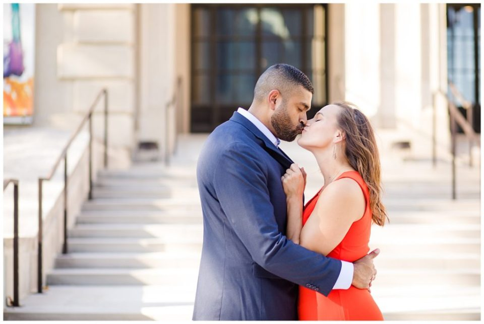 A photograph of an engaged couple holding and kissing each other romantically outside in front of a beautiful museum setting at the Columbus Museum of Art by Alayna Parker  - Columbus OH engagement photography