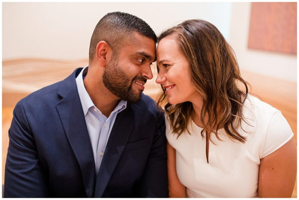 A picture of a closeup view of an engaged couple sitting close and tenderly smiling as they touch foreheads at the Columbus Museum of Art by Alayna Parker Photography Columbus  engagement photographer