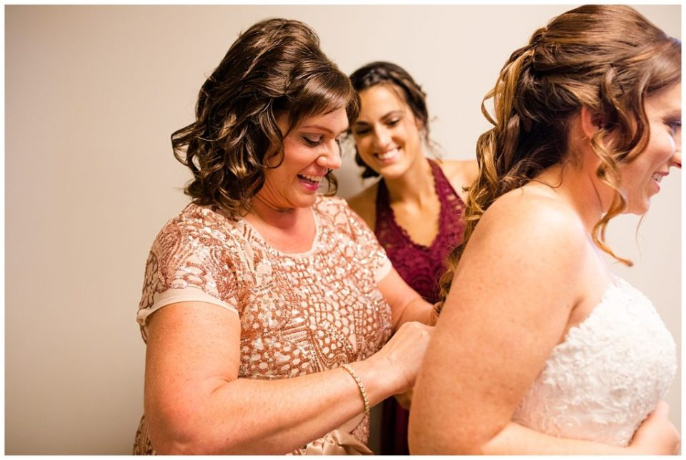 mother of the bride smiling as she helps bride get dressed at station 67
