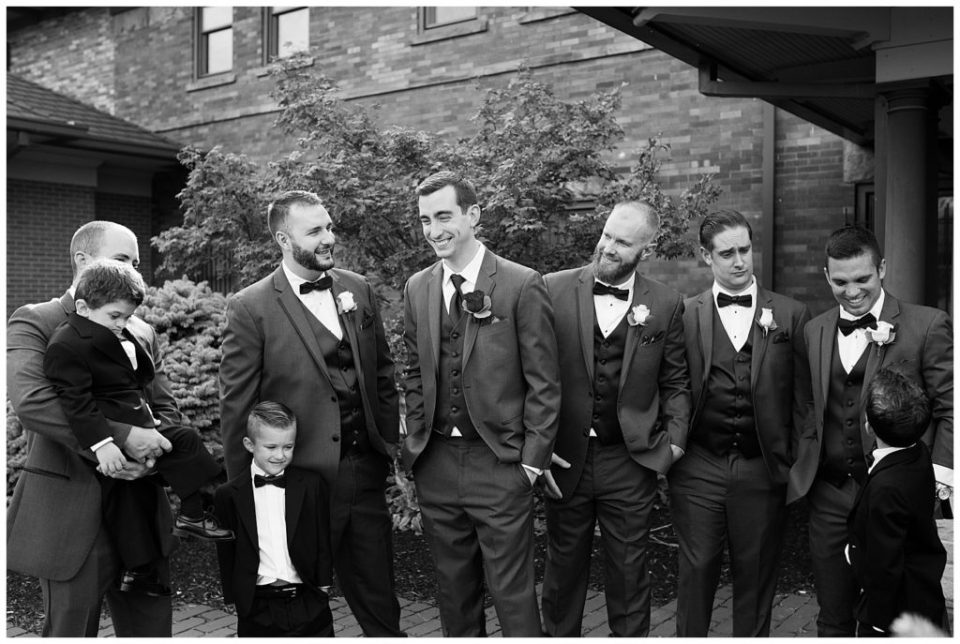 black and white image of groom and groomsmen laughing at station 67