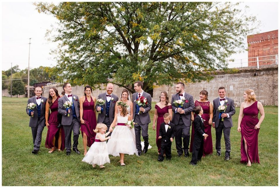 A photograph of the wedding party lined up outdoors, relaxing and having fun after the wedding at a Station 67 Columbus Ohio wedding by Alayna Parker Photography