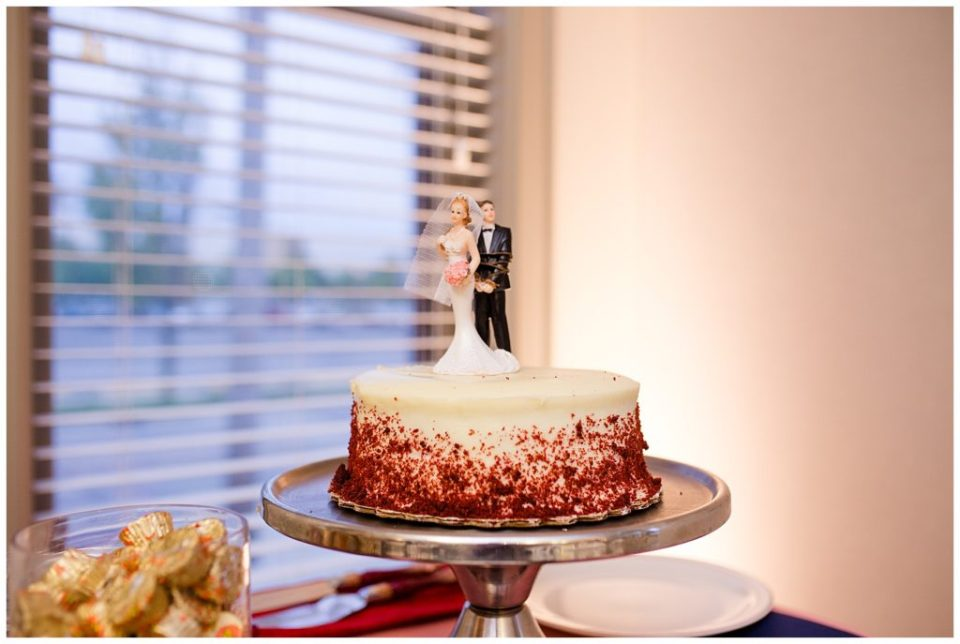 A picture of a closeup view of the wedding cake and topper at the wedding reception at a Station 67 Columbus OH wedding by Alayna Parker Photography