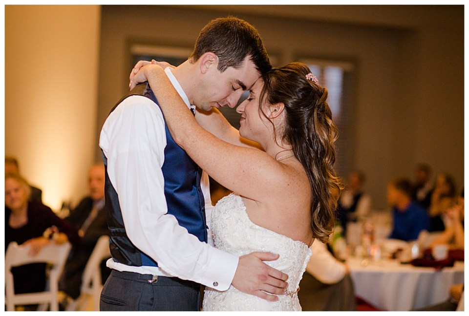 An image of a closeup view of the bride and groom holding each other romantically as they dance their first dance at the wedding reception at a Station 67 Columbus  wedding by Alayna Parker Photography