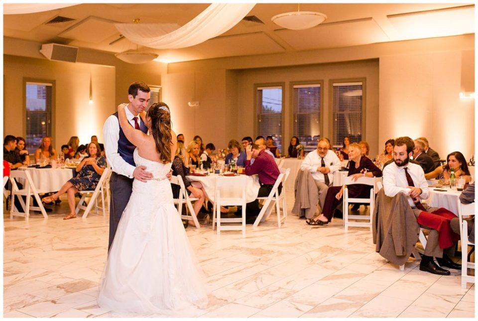 A photograph of the bride and groom dancing their first dance at their wedding reception while the guests look on at a Station 67 Columbus Ohio wedding by Alayna Parker Photography