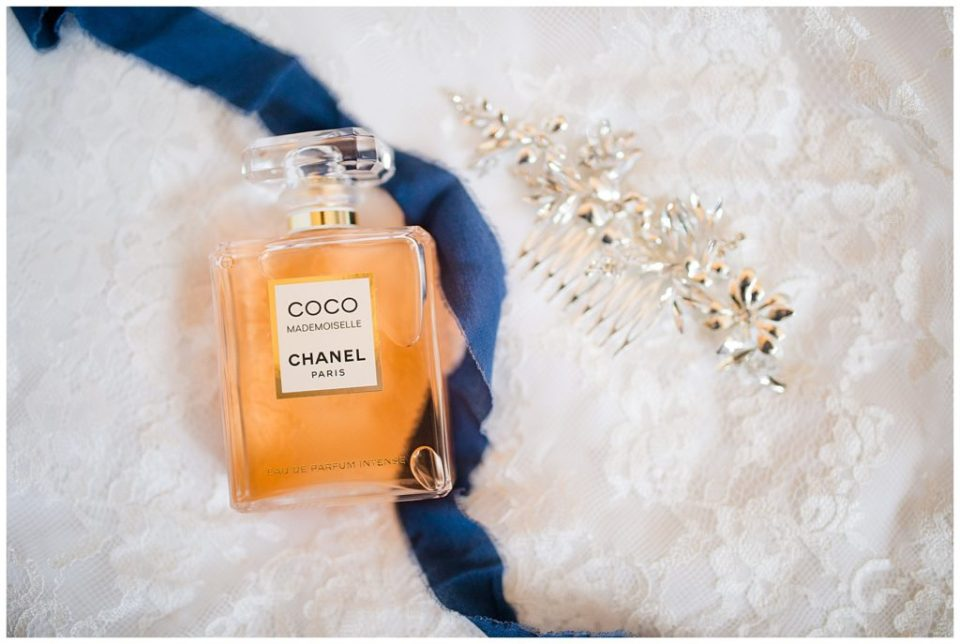 An image of a closeup view of a bride's special wedding details, showing her hair accessory, perfume, and sentimental blue item to wear by Columbus Ohio wedding photographer, Alayna Parker Photography
