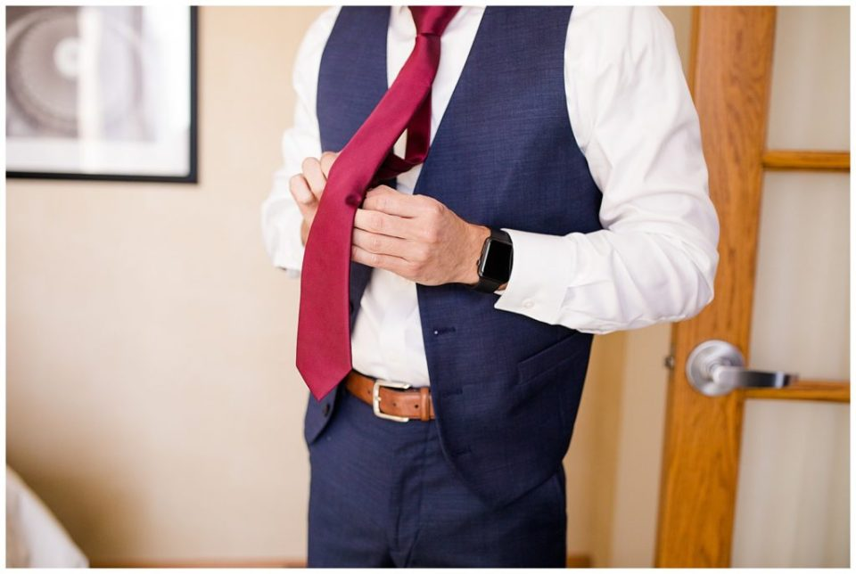 An image of a groom adjusting his tie as he prepares for his wedding ceremony by Columbus Ohio wedding photographer, Alayna Parker Photography