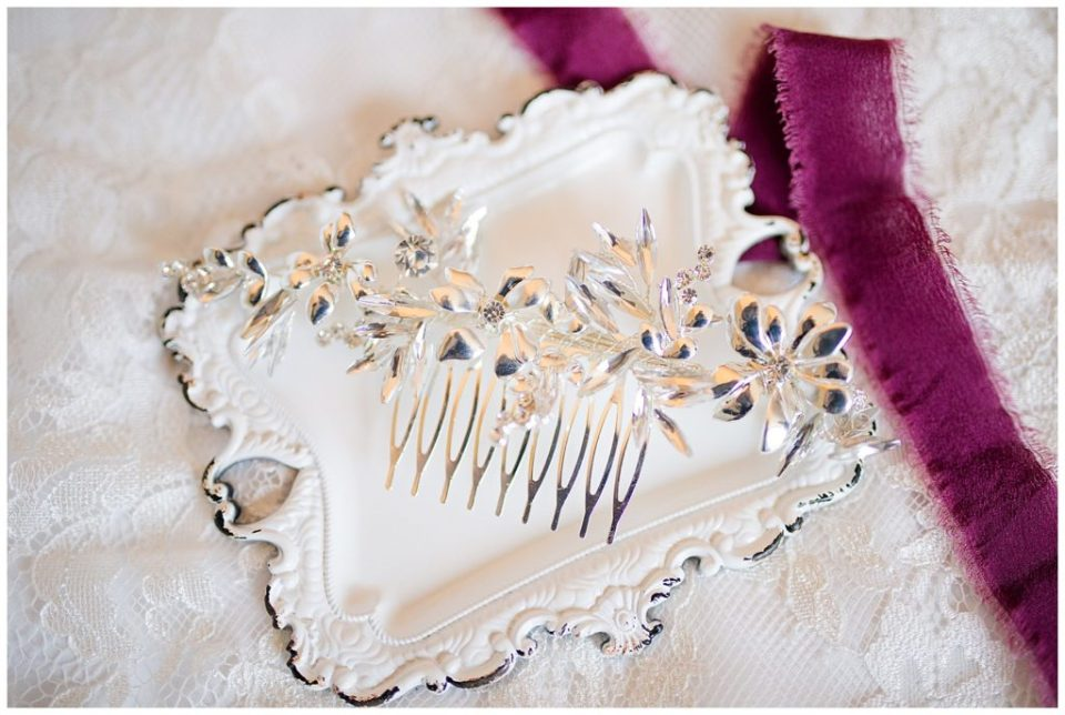 A photograph of a closeup of a bride's hair accessory resting on a background of her wedding dress by Columbus OH wedding photographer, Alayna Parker Photography