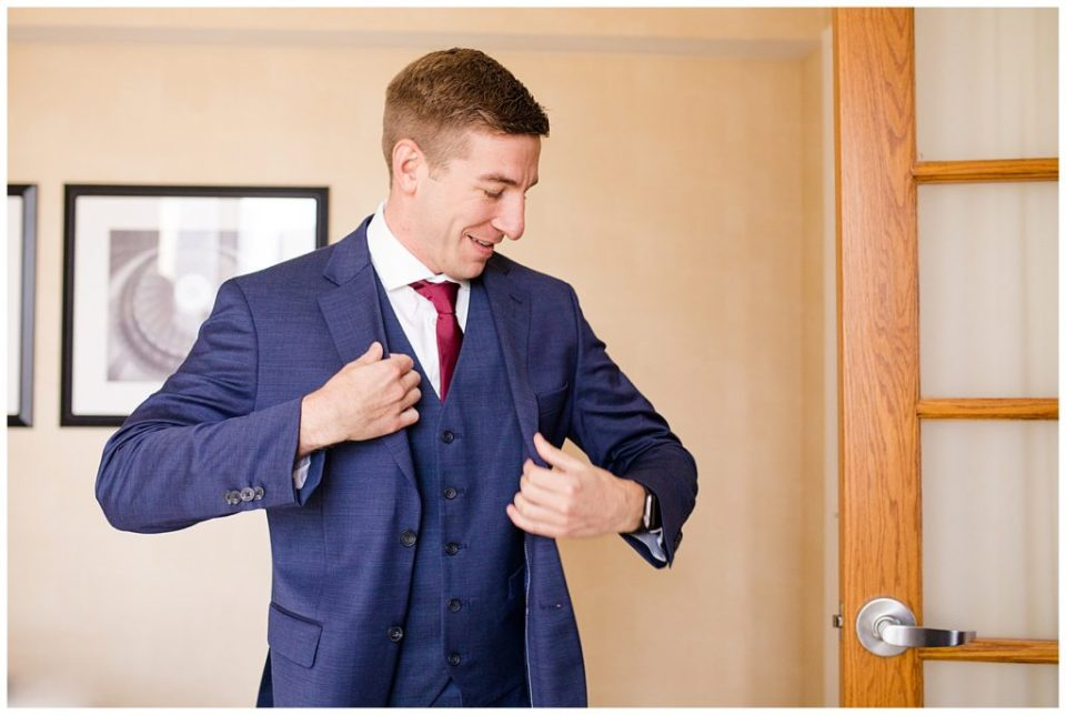 A picture of the groom putting on his tuxedo jacket as he is dressing for the wedding ceremony by Columbus  wedding photographer, Alayna Parker Photography