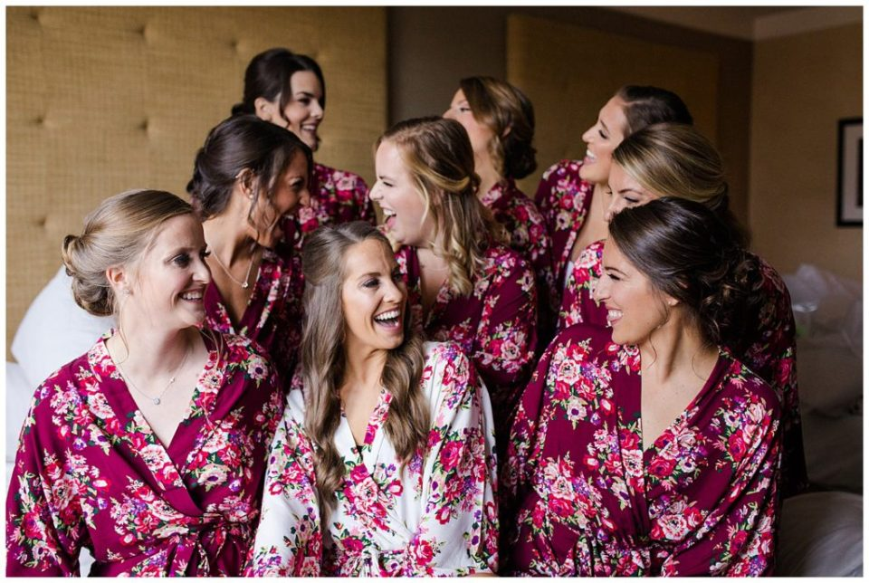 A photograph of a bride and her bridesmaids smiling and relaxing together in their matching robes before the wedding ceremony by Columbus OH wedding photographer, Alayna Parker Photography