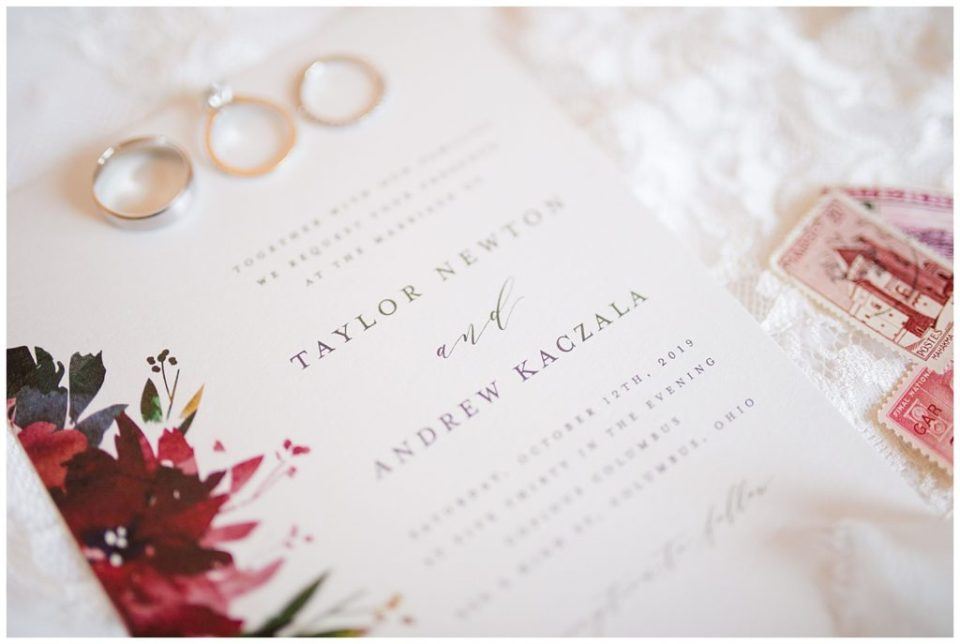 A photograph of a closeup of the beautiful wedding invitation and wedding rings by Columbus OH wedding photographer, Alayna Parker Photography