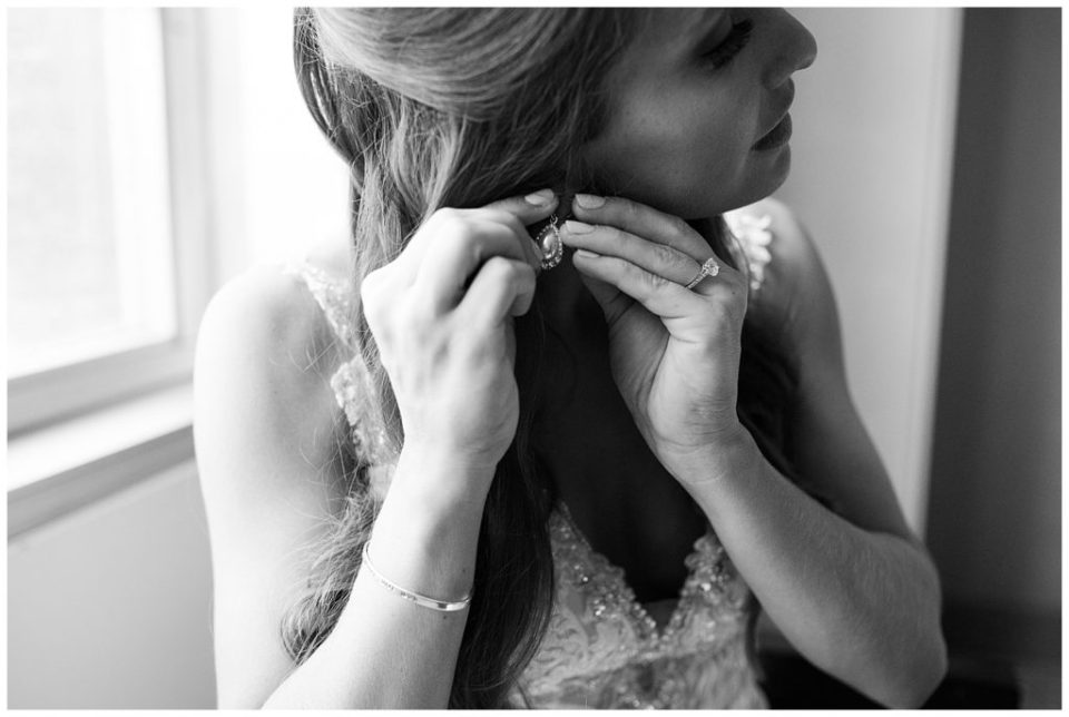 black and white image of bride putting in earring at renaissance hotel