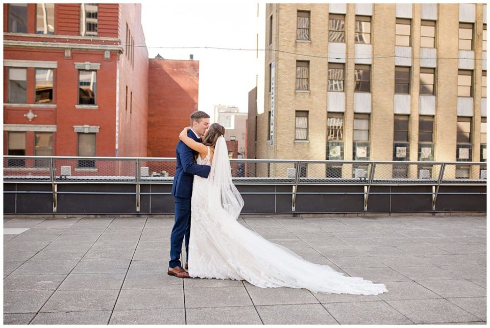 bride and groom kiss after first look on rooftop at renaissance hotel