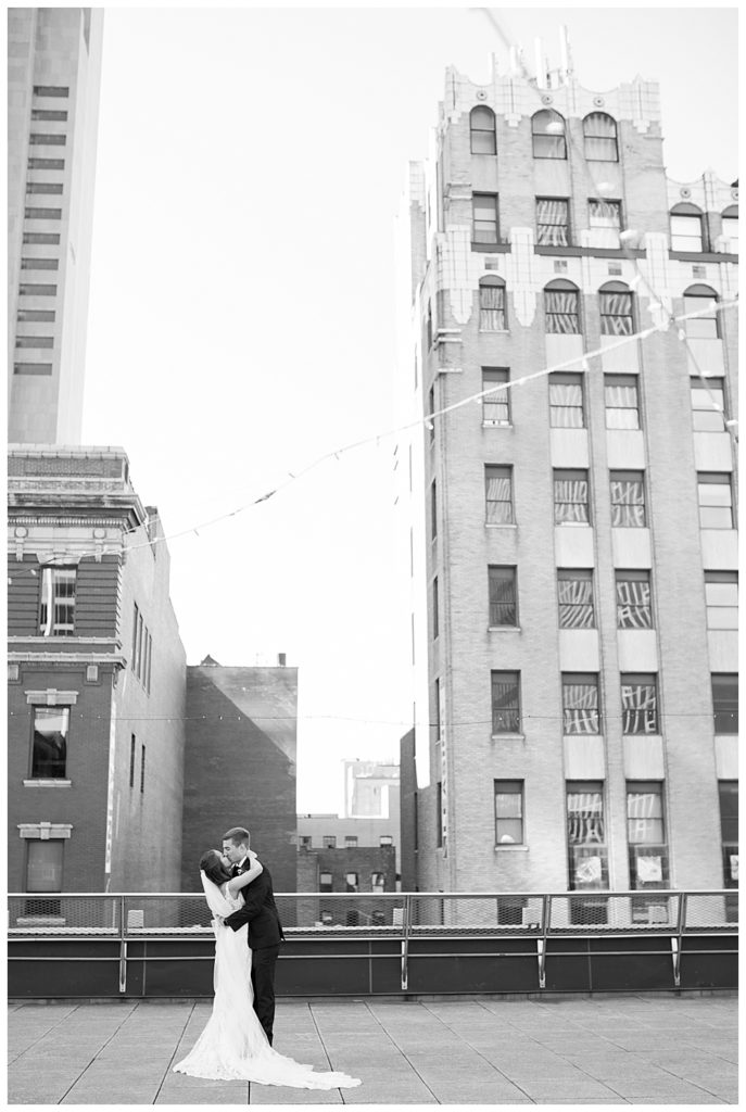 black and white image of bride and groom kissing after first look on rooftop at renaissance hotel