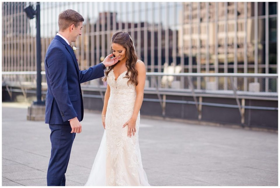 groom strokes bride's cheek on rooftop at renaissance hotel