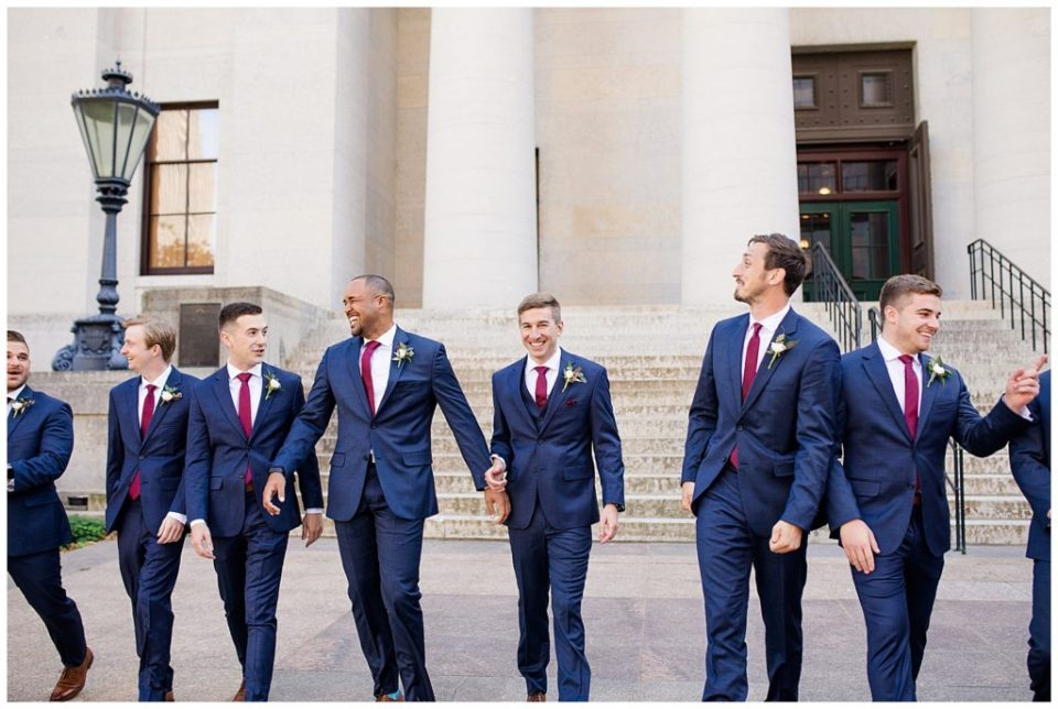 groom and groomsmen laughing and walking outside ohio statehouse