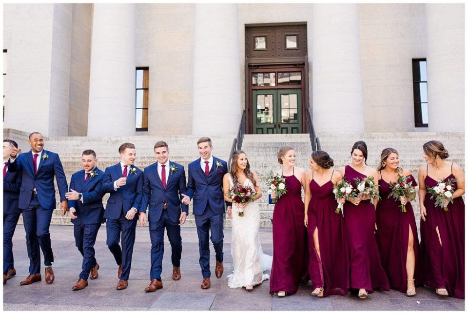 bride and groom and bridal party laughing and walking outside ohio statehouse