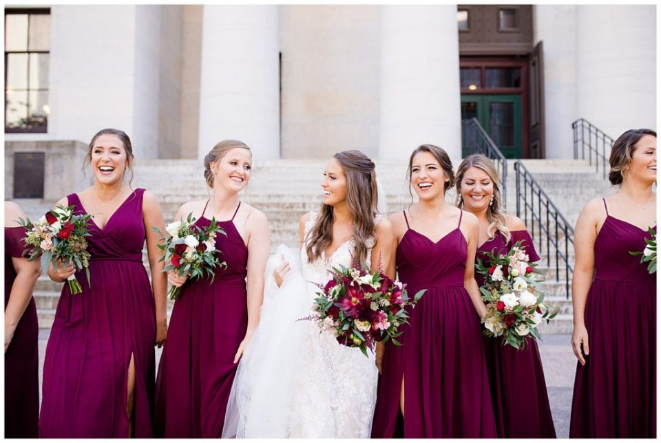 bride and bridesmaids laughing and talking while they walk outside ohio statehouse