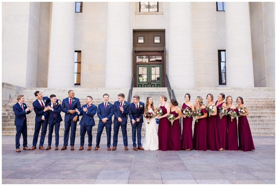 bride and groom and bridal party laughing and talking outside ohio statehouse