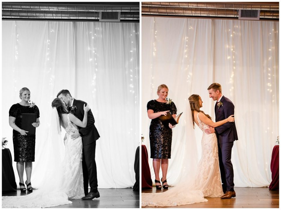 black and white image of bride and groom having first kiss at copius