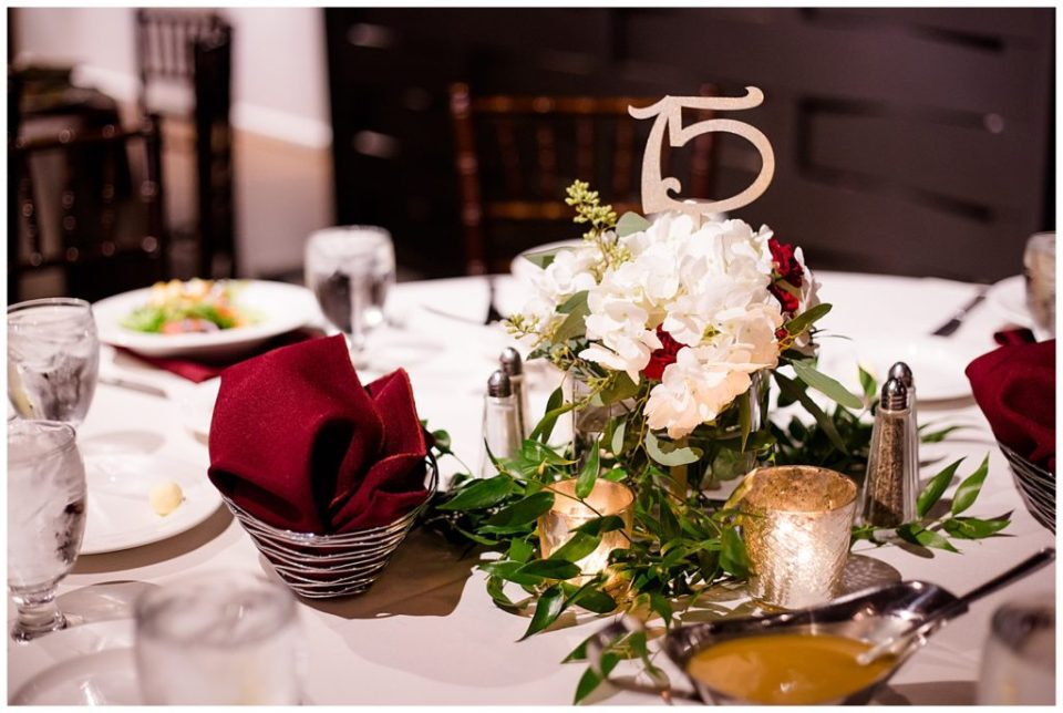 white and burgundy floral centerpiece at copius