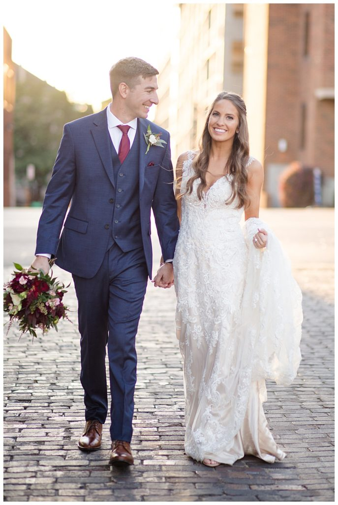 bride smiling at camera while groom smiles at bride in alley in downtown columbus