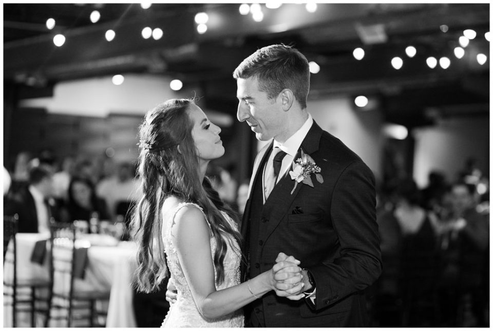 black and white image of bride and groom sharing first dance at copius