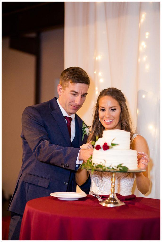 bride and groom cutting cake at copius