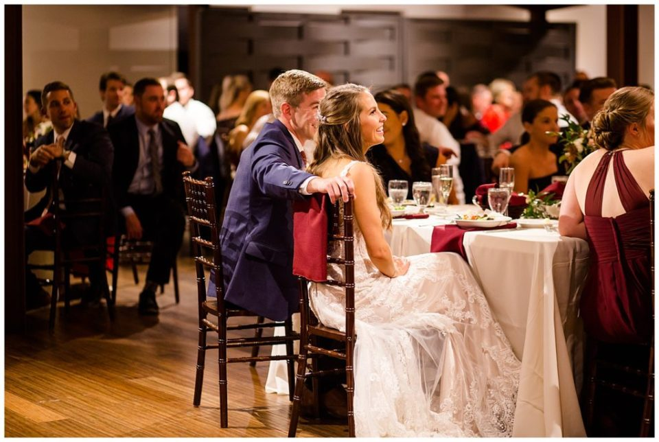 bride and groom laughing during father's speech at copius