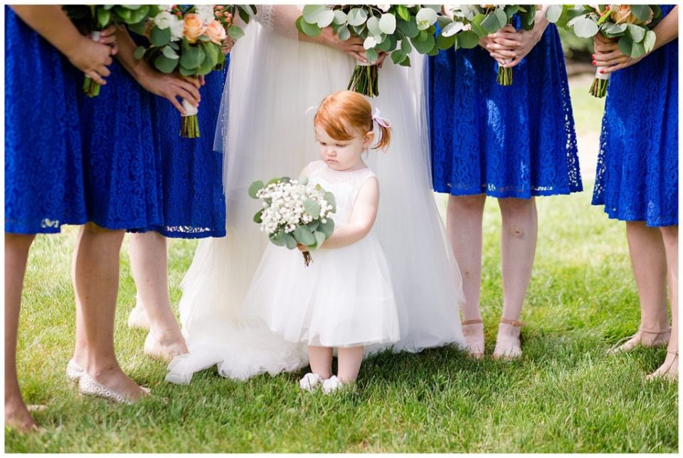 A photograph of the tiny, precious flower girl standing with her bouquet in front of the bride and her bridesmaids at a Nationwide Conference Center wedding by Columbus OH wedding photographer, Alayna Parker Photography