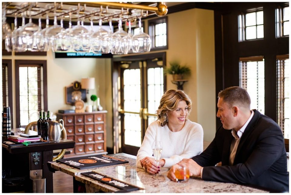 A photograph of an engaged couple sitting together, smiling and talking, in a classy club bar at Brookside Golf & Country Club by Columbus OH engagement photographer, Alayna Parker Photography