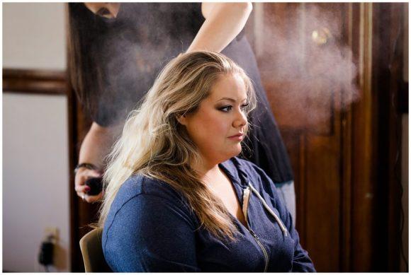 hair stylist hairsprays bride's hair at the postmark