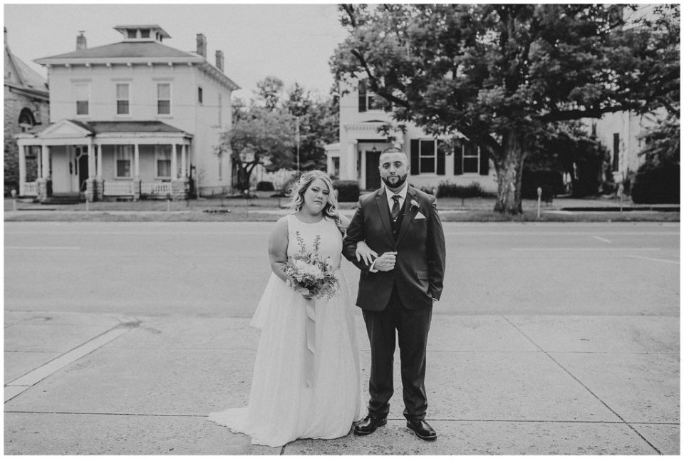 black and white image of bride and groom standing with arms links outside at the postmark