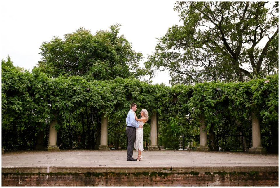 An image of an engaged couple at a distance embracing as they stand on a vintage veranda surrounded by columns and trees as they share time in a peaceful park by Alayna Parker Photography an engagement photographer in Columbus